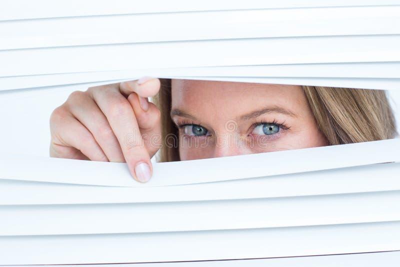 Mulher que espreita através das cortinas de rolo imagem de stock royalty free