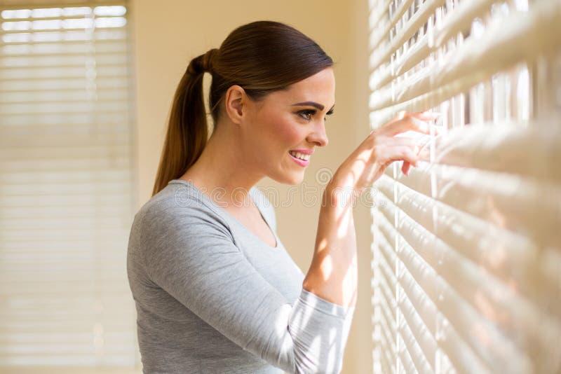 Mulher que espreita cortinas de janela fotografia de stock