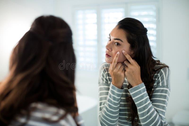 Mulher que espreme espinhas na frente do espelho do banheiro fotografia de stock