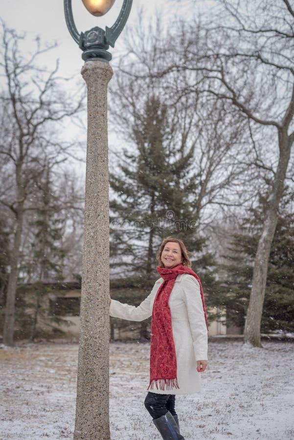 Mulher que está ao lado do cargo ornamentado da lâmpada que levanta para a foto na neve fotografia de stock royalty free