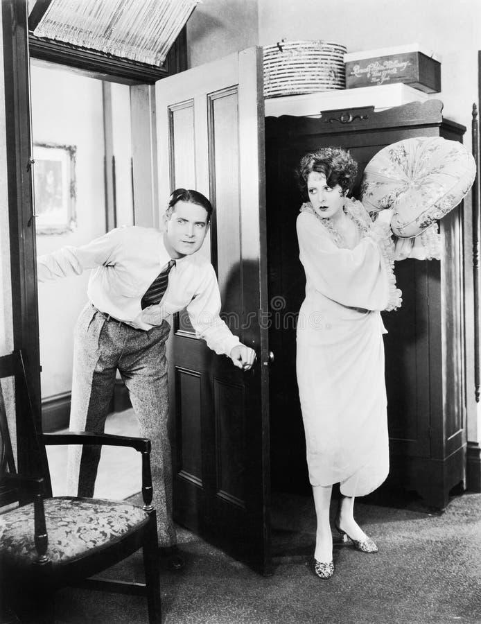 Mulher que está atrás de uma porta que tenta bater um homem com um descanso (todas as pessoas descritas não são umas vivas mais l imagens de stock