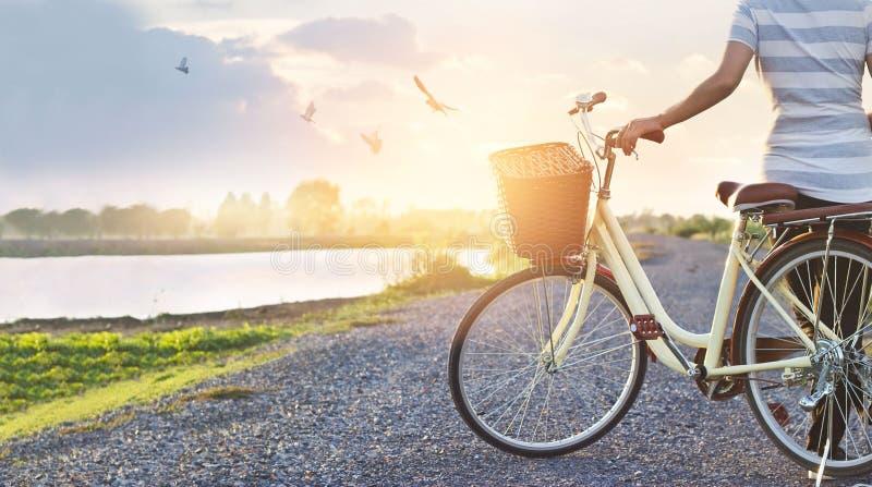 Mulher que está com a bicicleta do vintage, relaxando na natureza do por do sol do verão rural foto de stock royalty free