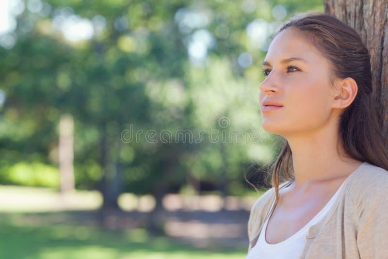 Mulher que está com ela para trás contra uma árvore foto de stock royalty free