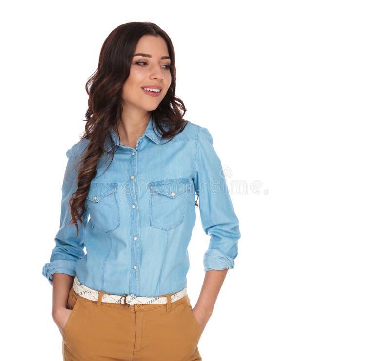 A mulher que está com mãos em uns bolsos olha afastado para tomar partido fotos de stock