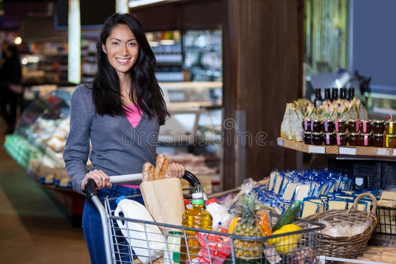 Mulher que está com o carrinho de compras na seção do mantimento imagem de stock royalty free