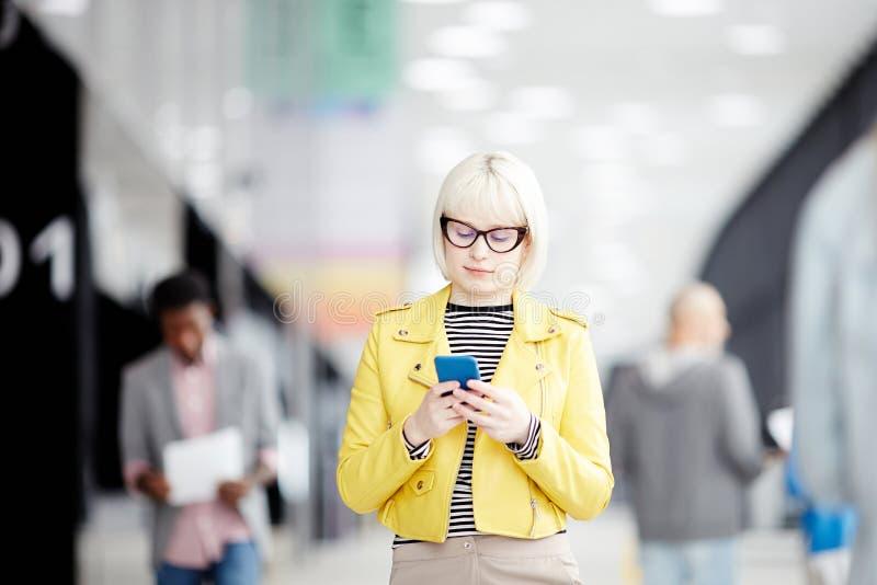 Mulher que está com o telefone no salão do escritório fotos de stock royalty free