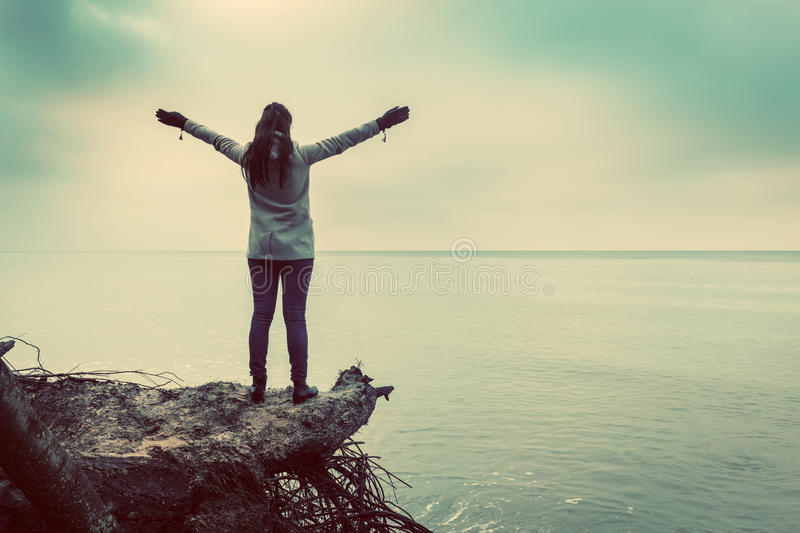 A mulher que está em árvore quebrada na praia selvagem com braços levantou a vista do mar imagens de stock