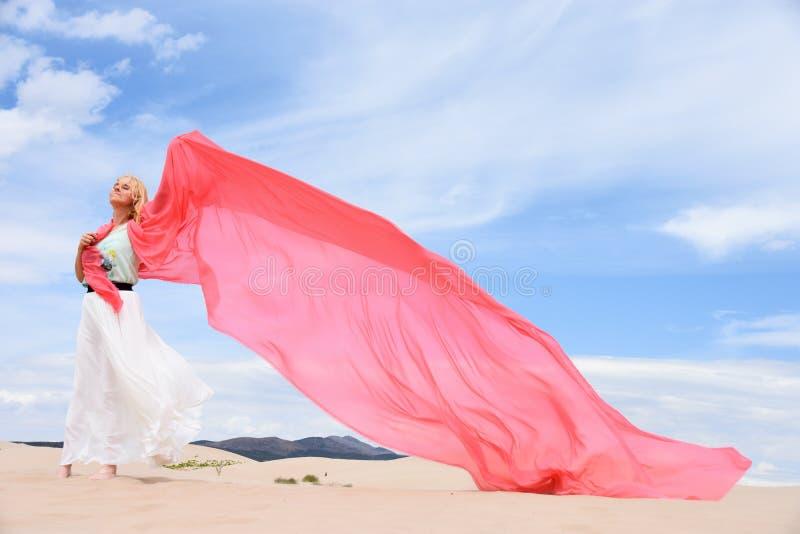 Mulher que está em dunas de areia fotos de stock royalty free