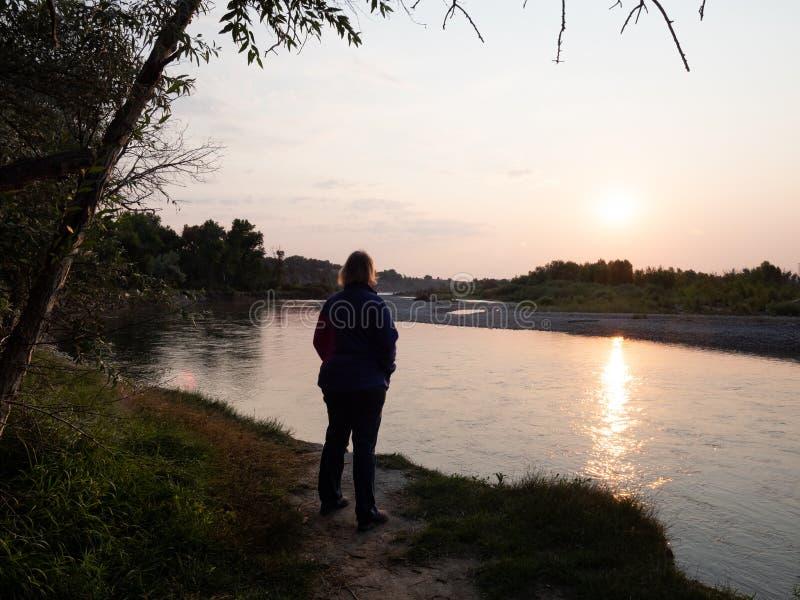 Mulher que está em um banco de rio no nascer do sol fotografia de stock