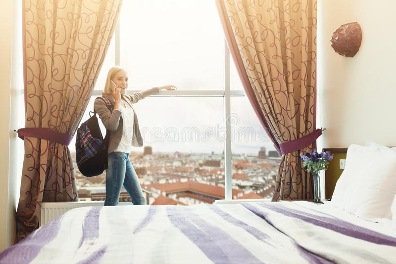 Mulher que está a janela próxima na sala de hotel imagem de stock royalty free