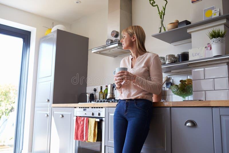 Mulher que está na cozinha com bebida quente foto de stock royalty free