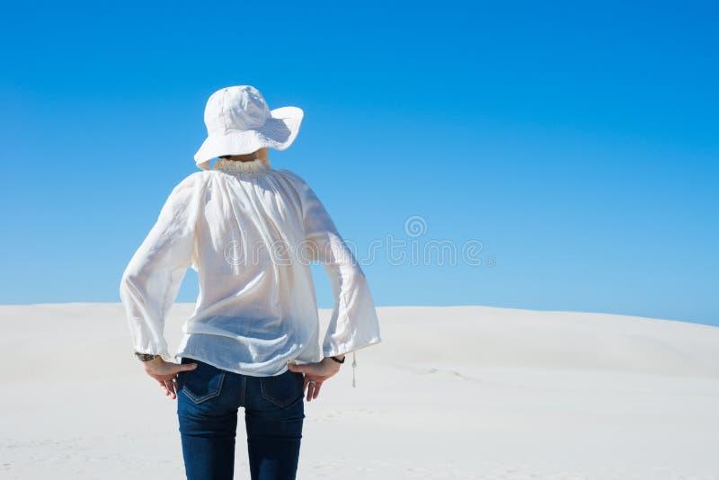 Mulher que está na duna de areia e que olha afastado fotografia de stock royalty free