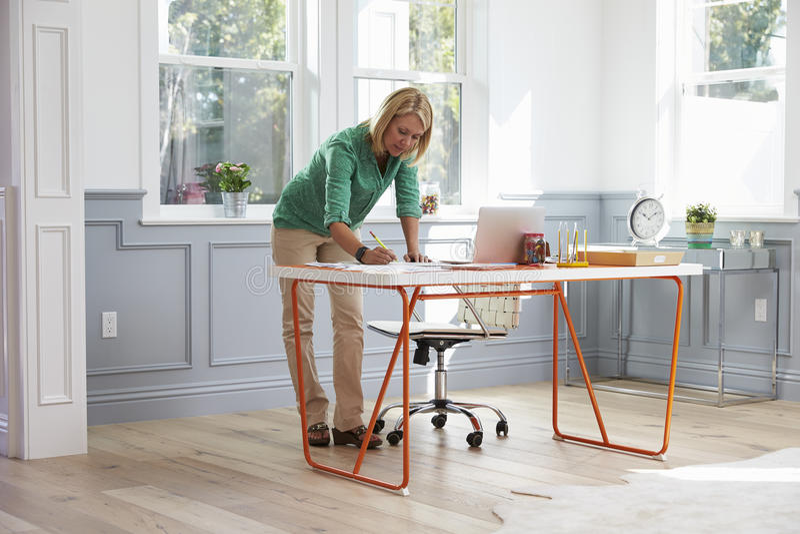 Mulher que está na mesa que trabalha no portátil no escritório domiciliário imagem de stock royalty free