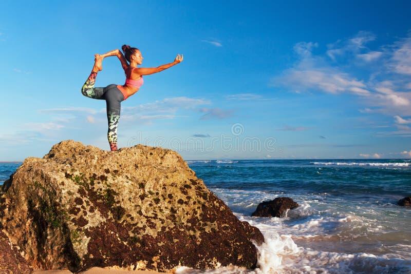 Mulher que está na pose da ioga na rocha da praia do mar imagens de stock