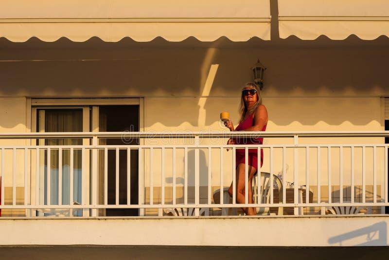 Mulher que está no balcão cedo na manhã durante a SU fotografia de stock royalty free