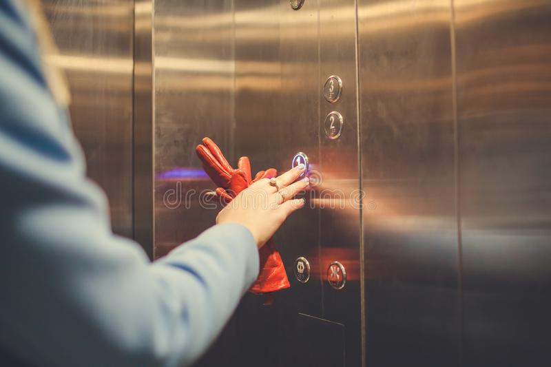 Mulher que está no elevador e que pressiona o botão foto de stock