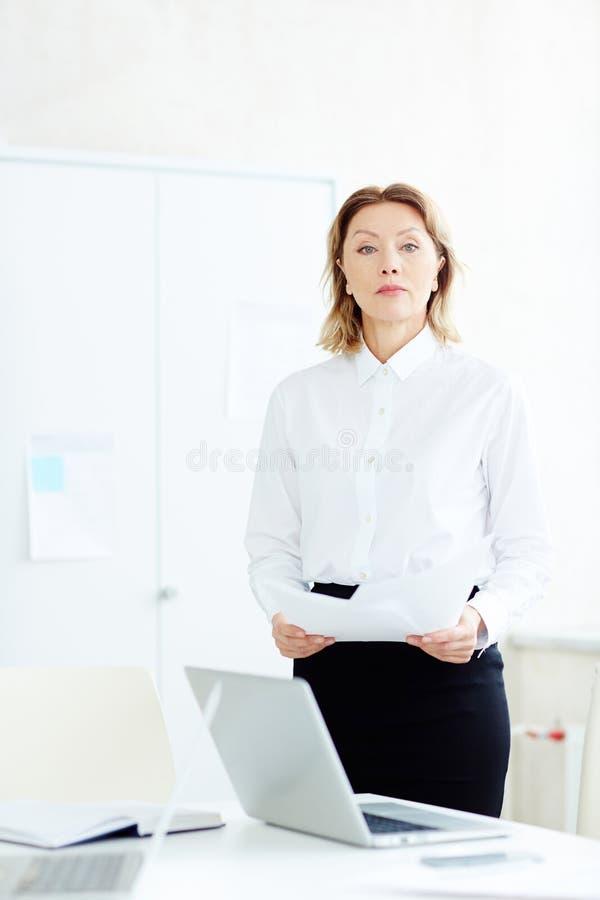 Mulher que está no escritório fotografia de stock royalty free