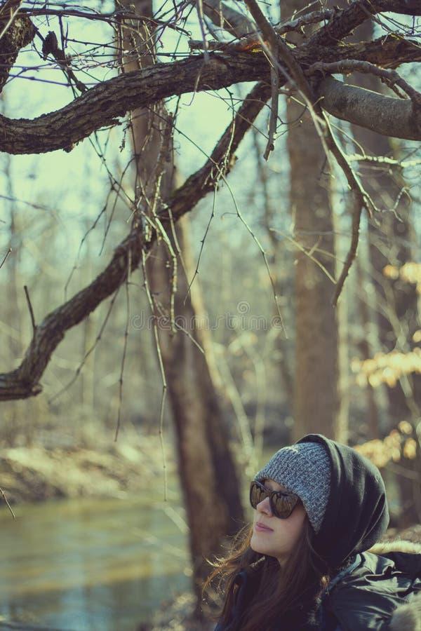 Mulher que está no riverbank nas madeiras imagem de stock