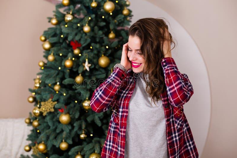 Mulher que está perto da árvore de Natal foto de stock royalty free