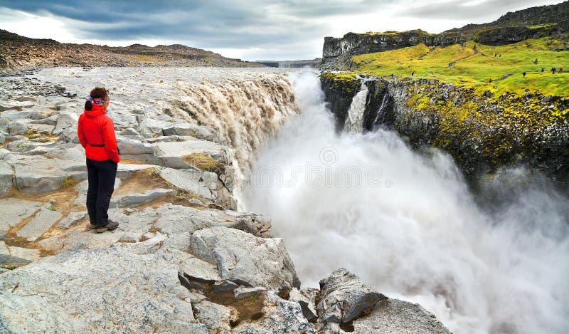 Mulher que está perto da cachoeira famosa de Dettifoss no parque nacional de Vatnajokull, Islândia fotografia de stock