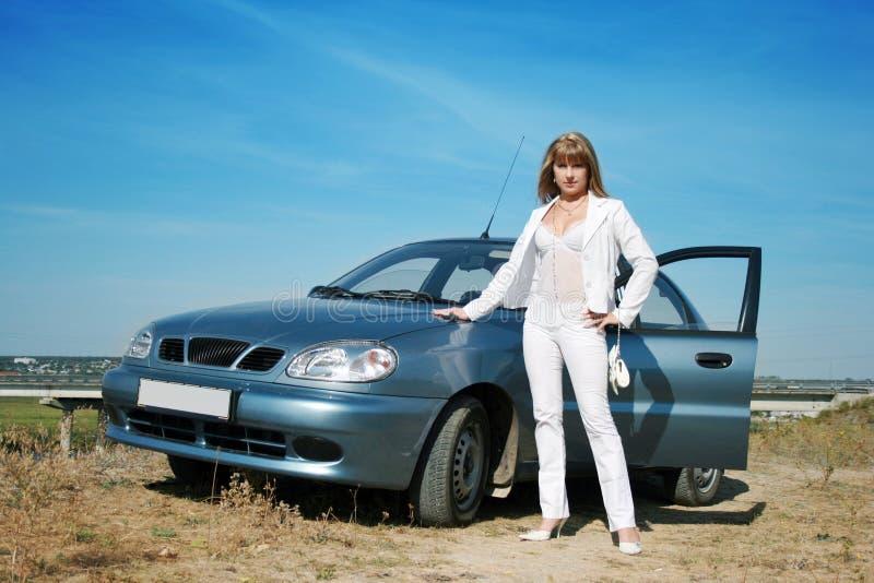 Mulher que está perto do carro azul imagem de stock royalty free