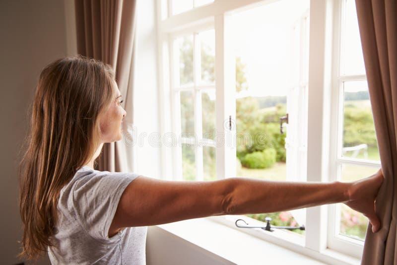 Mulher que está por cortinas da janela e de abertura do quarto imagem de stock royalty free