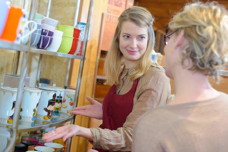 Mulher que está sendo ajudada a escolher o copo na loja fotografia de stock
