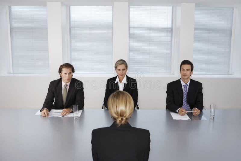 Mulher que está sendo entrevistada por executivos fotos de stock royalty free