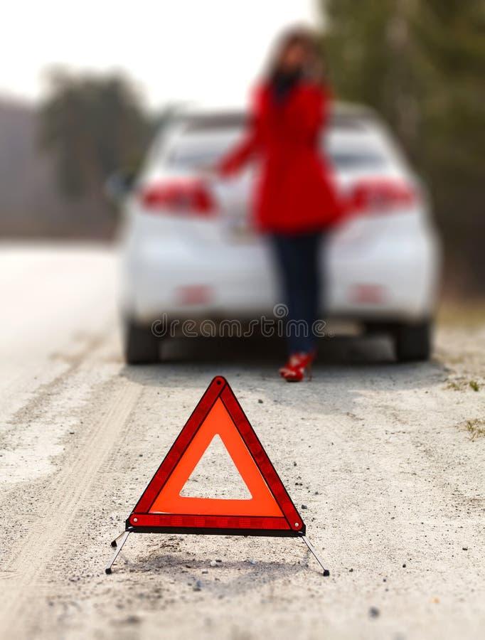 A mulher que estão pelo carro quebrado e o triângulo de advertência assinam fotografia de stock royalty free