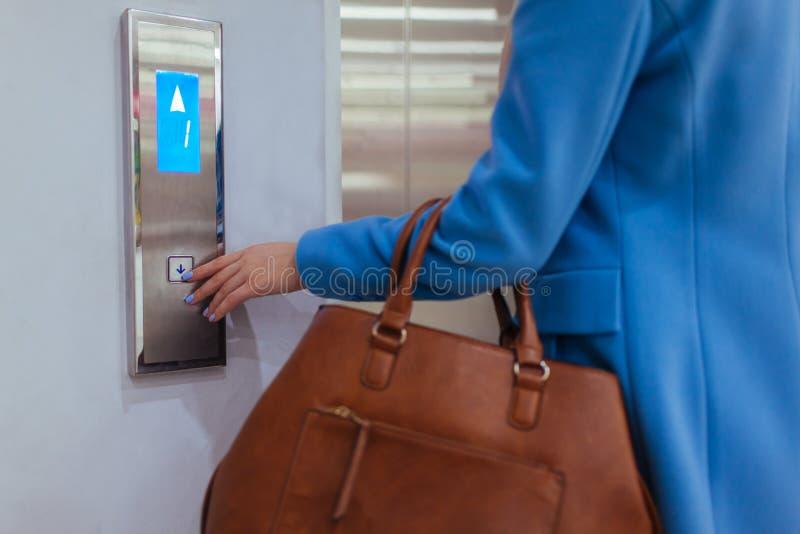 Mulher que est? no elevador e que pressiona o bot?o fotografia de stock royalty free
