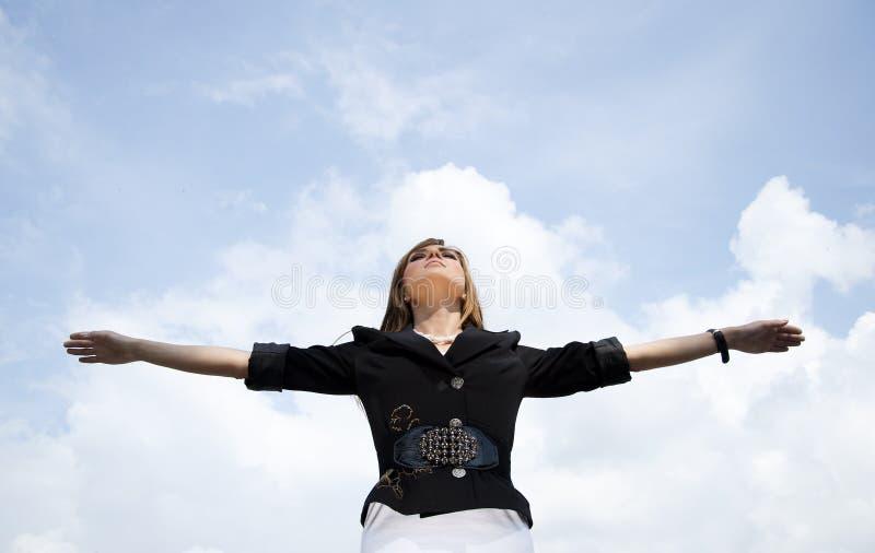 A mulher que estica as mãos aspira no céu foto de stock