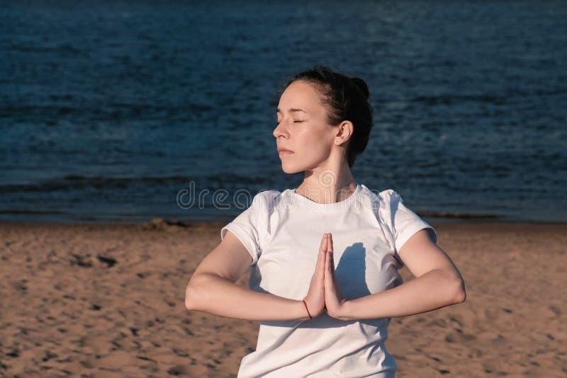 Mulher que estica a ioga na praia pelo rio na cidade Opinião bonita da cidade Pose de Namaste fotos de stock royalty free