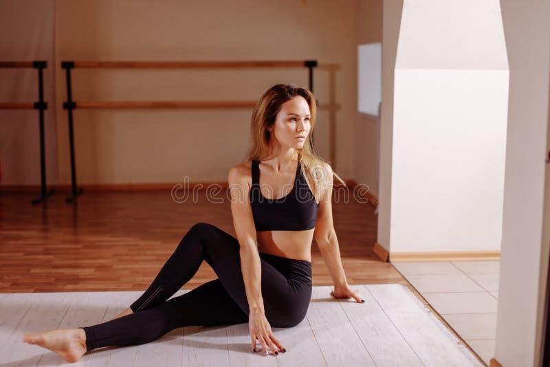 A mulher que estica a menina magro nova assentada da torção espinal faz o exercício foto de stock royalty free