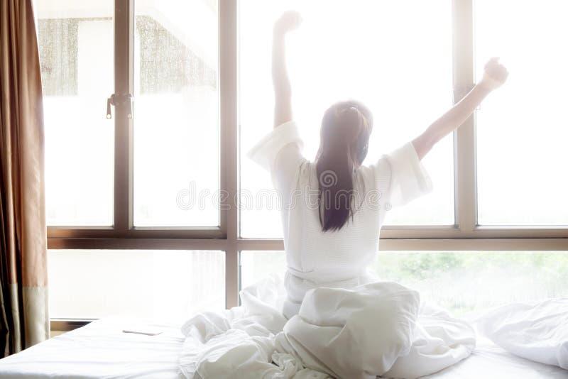 A mulher que estica na cama após acorda foto de stock