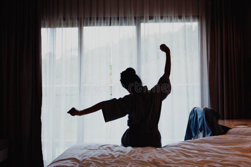 A mulher que estica na cama após acorda, vista traseira imagem de stock