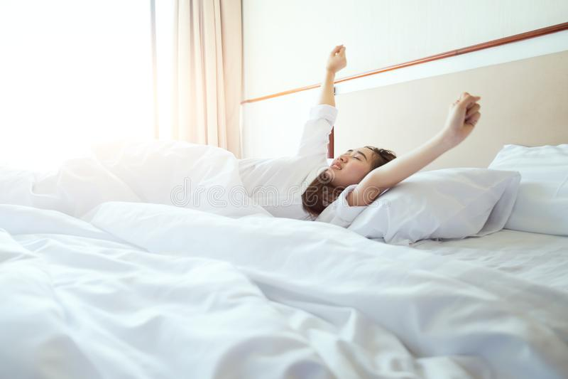Mulher que estica na cama após acordar, luz solar na manhã fotografia de stock
