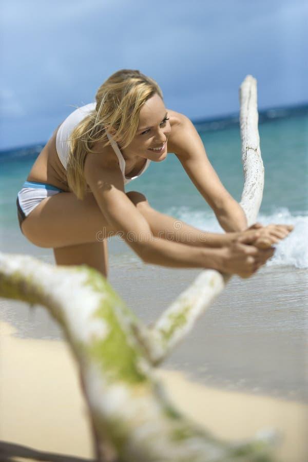 Mulher que estica na praia. foto de stock