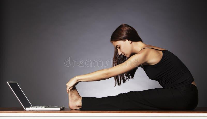 Mulher que estica no fornt do portátil. foto de stock royalty free