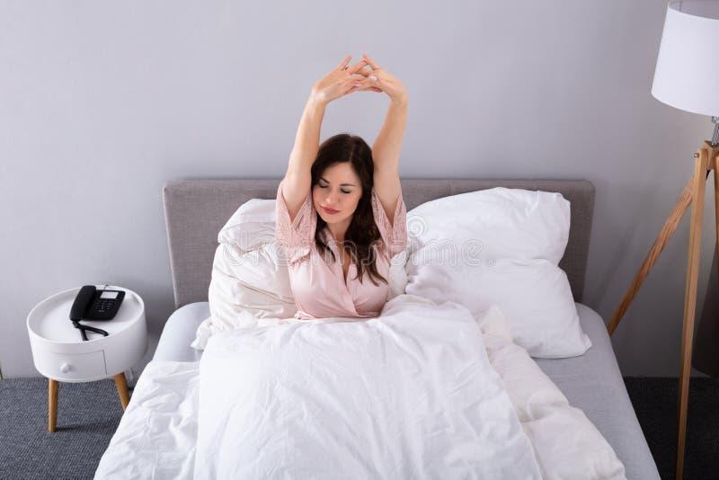 Mulher que estica seus bra?os na cama foto de stock royalty free