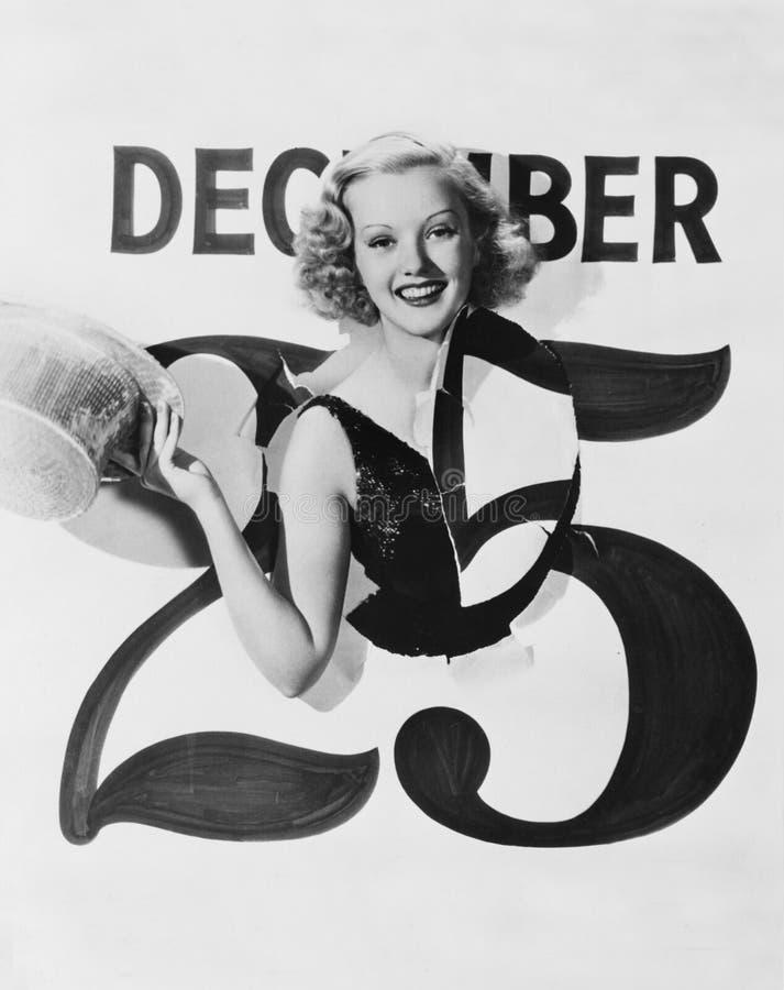 Mulher que estoura através do calendário no dia de Natal (todas as pessoas descritas não são umas vivas mais longo e nenhuma prop imagens de stock