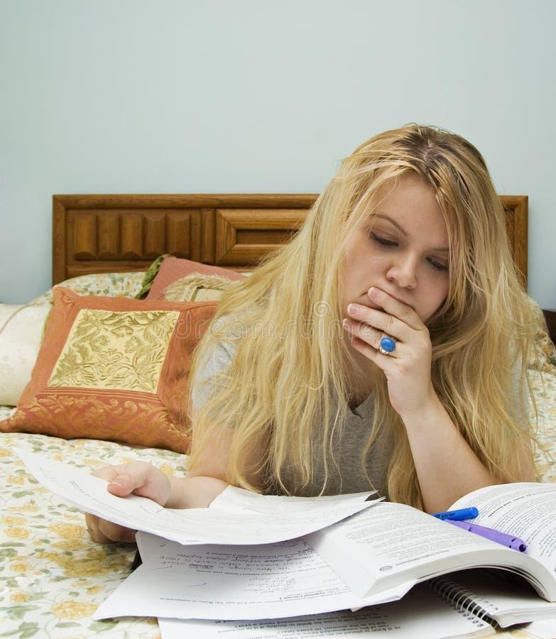 Mulher que estuda na cama imagens de stock