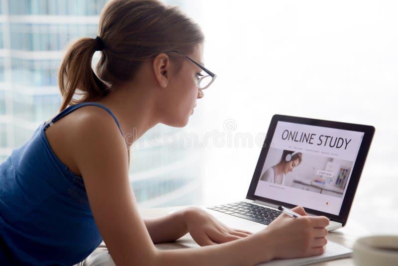 Mulher que estuda o curso educacional em linha no Internet usando o lapto fotos de stock royalty free