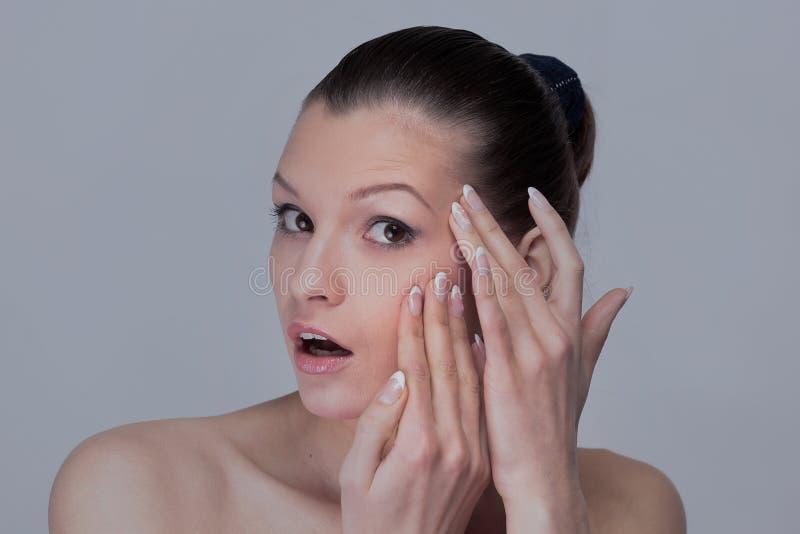 Mulher que examina seus cara e enrugamentos que podem aparecer, isolados fotos de stock royalty free