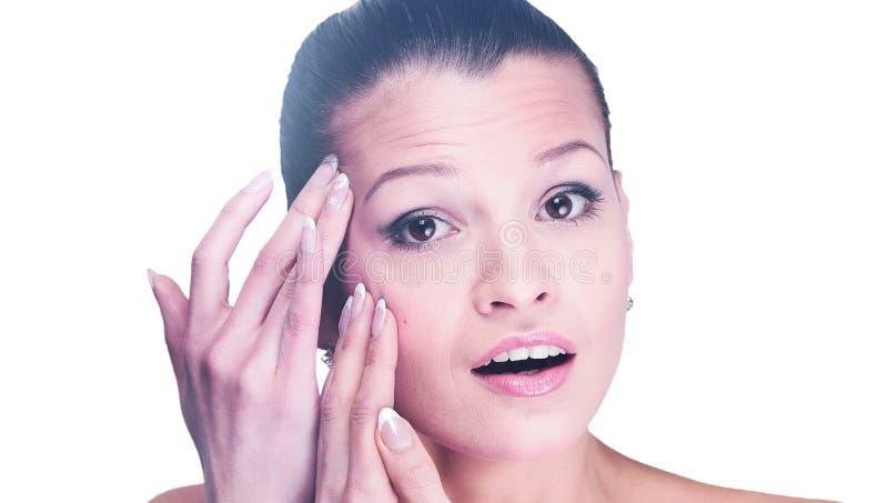 Mulher que examina seus cara e enrugamentos que podem aparecer, isolados fotografia de stock royalty free