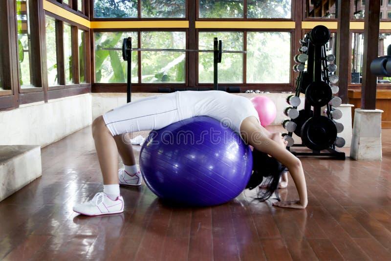 Mulher que excercising com esfera suíça foto de stock royalty free