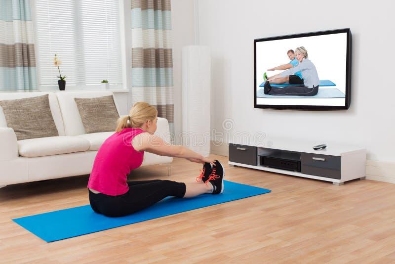 Mulher que exercita ao olhar o programa na televisão imagens de stock royalty free