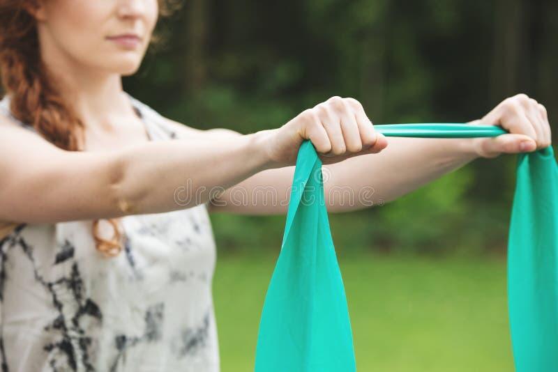 Mulher que exercita com faixa do estiramento imagens de stock