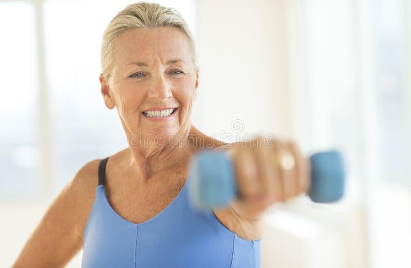 Mulher que exercita com pesos em casa imagens de stock