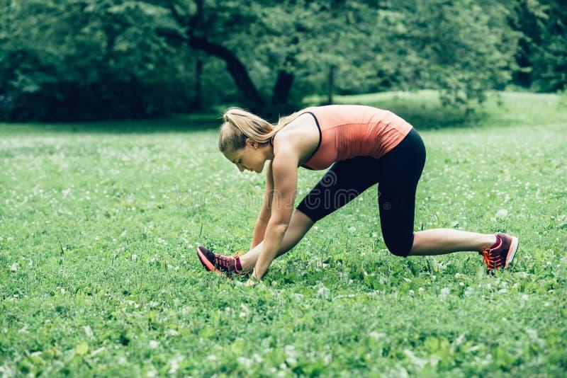 Mulher que exercita e que estica no gramado da floresta da natureza fotografia de stock royalty free