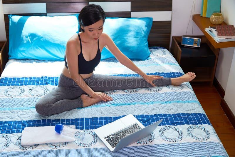 Mulher que exercita na cama fotografia de stock royalty free